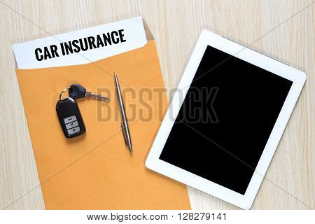 Top view of Car insurance in envelope with car remote key and tablet.