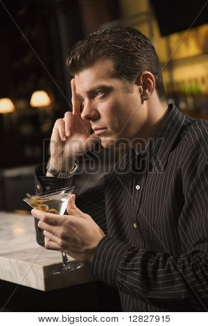 Side view of mid adult Caucasian man holding martini with hand to head thinking.