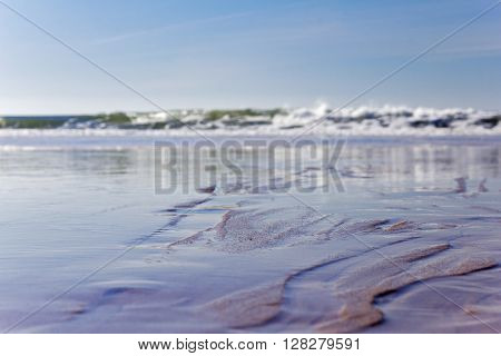 Closeup to the sand in the beach in a low tide with waves blurred in the background