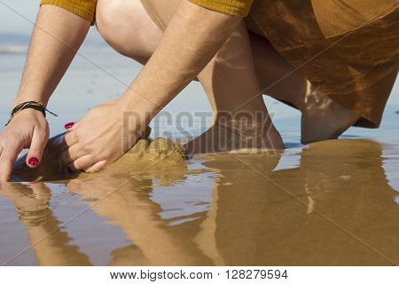 Girl playing in the wet sand in the beach in a sunny day.