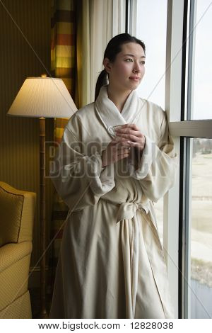 Taiwanese mid adult woman in bathrobe looking out window holding coffee cup.