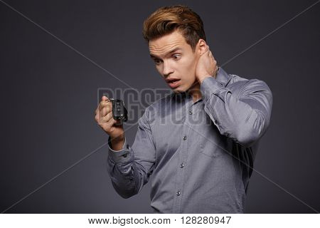 Businessman gives the keys to the car. Isolated on grey