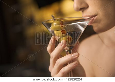 Close up of mid adult Caucasian woman drinking a martini with three olives.