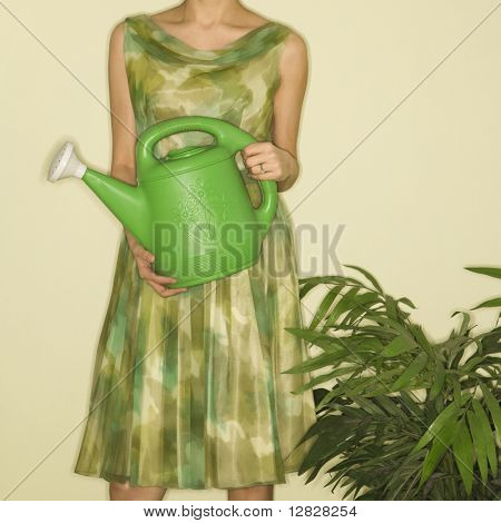 Pretty Caucasian mid-adult woman wearing vintage dress standing next to houseplant holding green watering can.