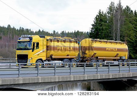 FORSSA, FINLAND - APRIL 30, 2016: Yellow Volvo FH tank truck drives along bridge on a scenic highway in South of Finland.