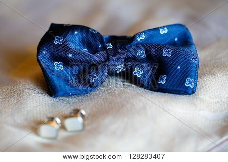 Bowtie and cuff links on textil background