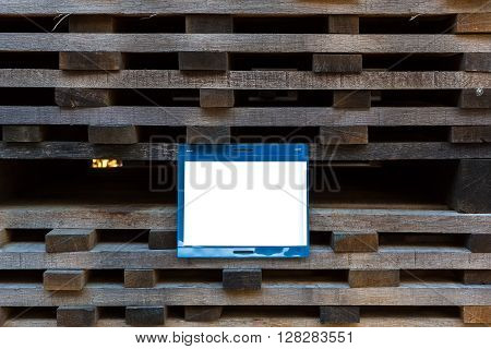 The treated plank stacked in piles to dry with a blank white sign on which can be located your text