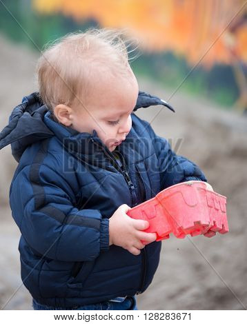Toddler boy looking at a playing with a sandbox toy.