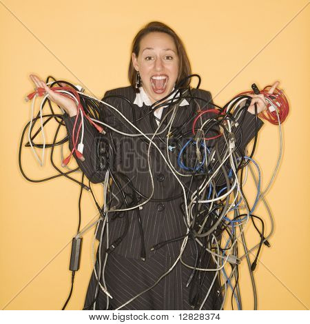 Caucasian businesswoman smiling holding pile of tangled cords and wires.