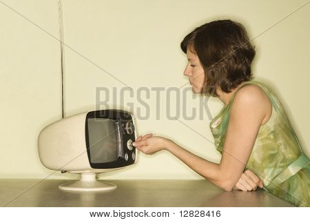 Seitenansicht einer hübschen kaukasischen adult Woman sitting at 50er retro Essecke set drehen alt televsio