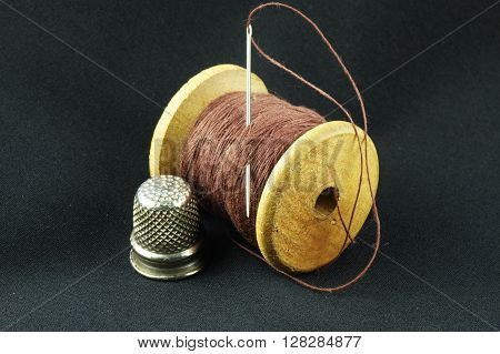 Wooden spool of thread with a needle and a thimble on a dark fabric.