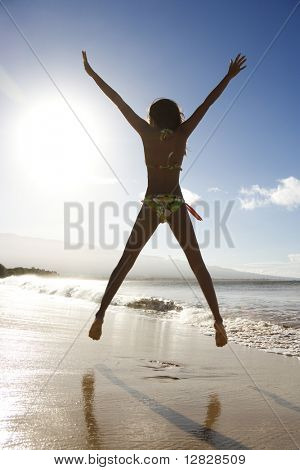 Back view of girl in bikini jumping enthusiastically on beach in Maui, Hawaii, USA.