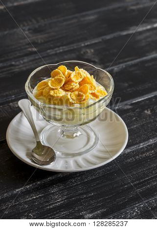 Pear with natural yoghurt corn flakes and honey - a delicious dessert breakfast or snack . On a dark wooden background