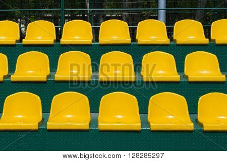 a yellow seats on the green tribune