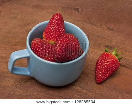 Fresh strawberries in a teal blue cup on a wooden background texture