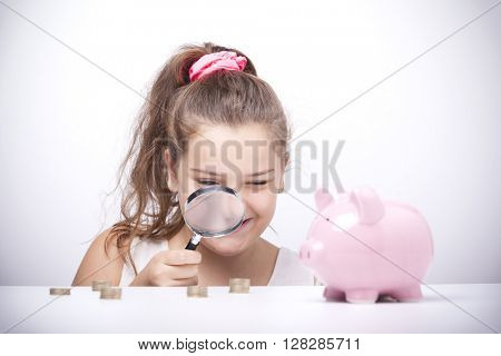 Little girl with a magnifying glass and looking to the savings