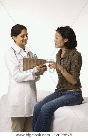 Indische Frau Doktor mit asiatischen Frau Patienten.