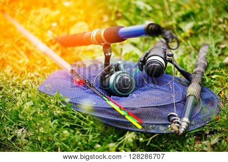 Fishing rods and tackle for fishing. Lays on the green grass