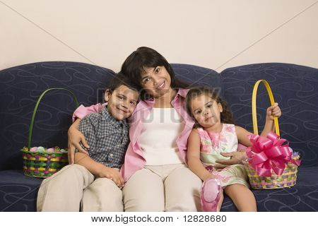 Family sitting on couch with Easter baskets smiling and looking at viewer.