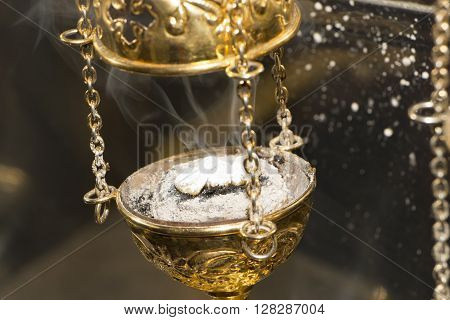 Christian Church brass thurible liturgy censer with coal ash smoke and incense in it. Closeup. Selective focus.