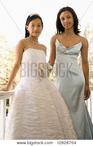 A portrait of a African-American maid of honor and Asian bride leaning against railing.