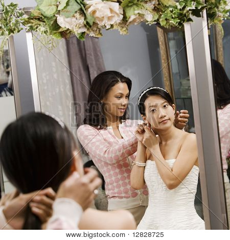 African-American woman helping Asian bride with hair.