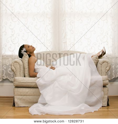 African-American bride lying on love seat.