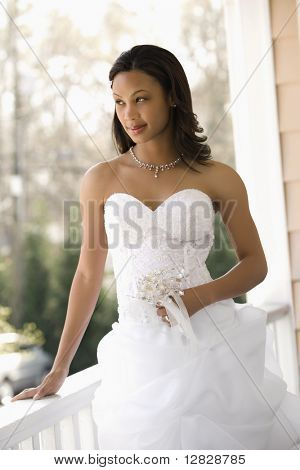 Portrait of African-American bride leaning against railing.