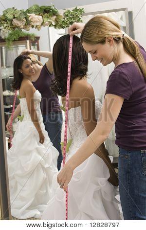 Caucasian seamstress measuring African-American bride in bridal shop.