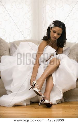 African-American bride placing shoe on foot.