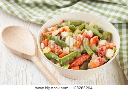 A mixture of assorted frozen vegetables in a bowl and with wooden spoon on white wooden table