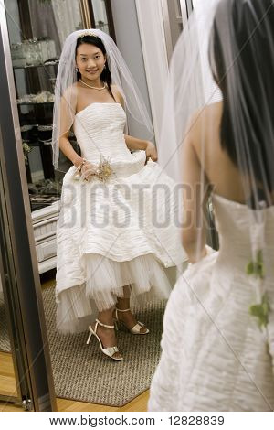 Asian bride admiring shoes in mirror.