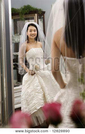Asian bride admiring dress in mirror.