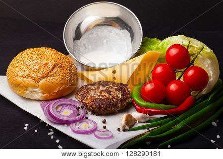 Exploded view of a hamburger on a black background. Ingredients. The process of assembling a hamburger.