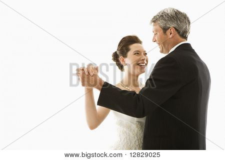 Portrait of Caucasian groom and Asian bride dancing.
