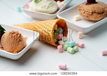 Ice cream sundae and waffle cone with candies