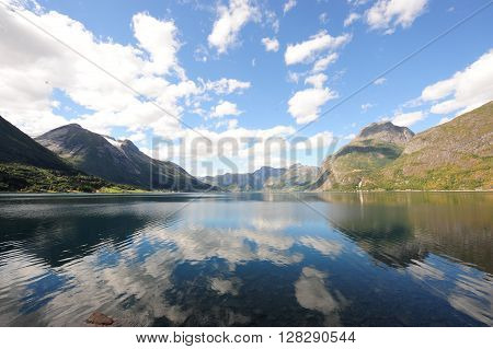 General view of Hjelle fjord and mountains in Norway showing the fjord with reflection of the sky in the water