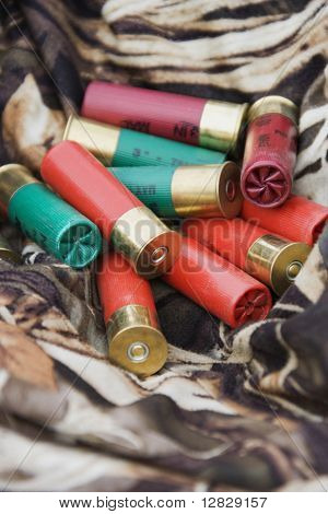 Still life shot of shotgun shells against camouflage clothing.