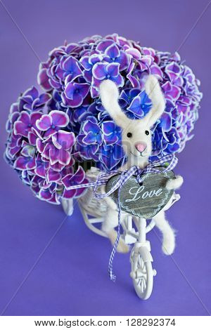 Felted wool toy.Woolen handmade toy bunny on a bicycle with hydrangea flowers, purple background .
