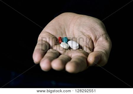 closeup of the hand of a young man with some different pills on a black background