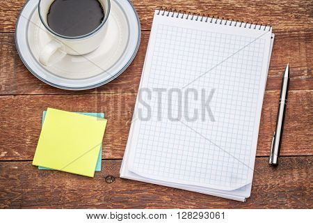 blank spiral notebook, sticky notes and a cup of coffee against rustic wood
