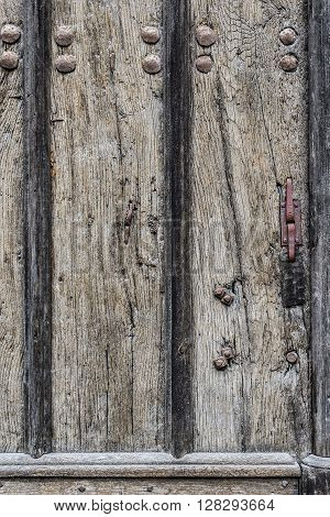 Weathered wooden door background with a metallic rusty rivets and screws.