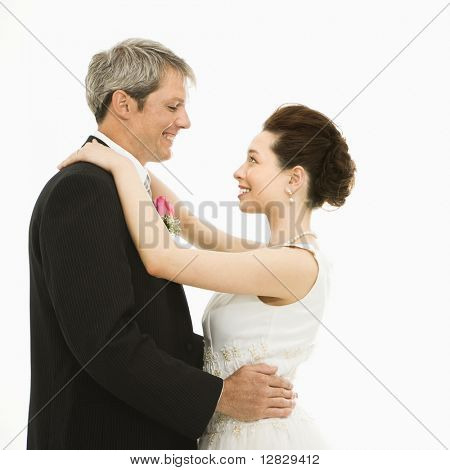 Caucasian groom and Asian bride dancing.