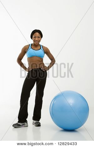 African American young adult Woman smiling at Viewer mit Händen an den Hüften neben gymnastikball.