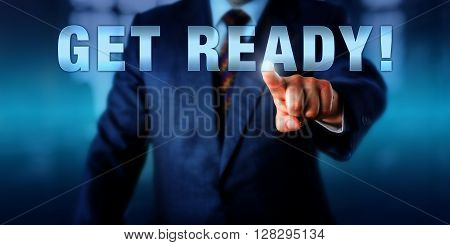 Corporate coach is touching GET READY! on a virtual interactive display. Motivational appeal call to action and business concept for preparation in anticipation of future events.