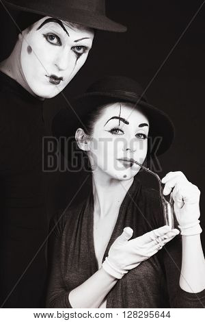 Two Mimes In Hats On Black Background