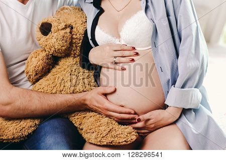 Pregnant Woman With Her Husband Holding Belly And A Soft Toy Bear