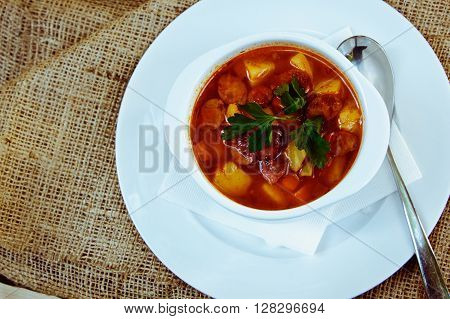 Beautiful Red Soup With Sausage In A White Plate With Spoon And Saucer. Restaurant Supply
