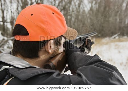 Caucasian male aiming shotgun out towards woods.