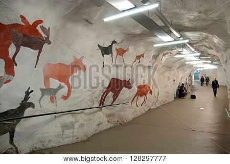 HELSINKI, FINLAND - APRIL 16, 2011: People walk and play accordion in the tunnel with pictures of animal. Tunnel to the entrance of the Kaisaniemi Metro Station